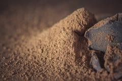 Chocolate, sólidos del cacao y polvo de cacao oscuros sobre fondo de madera Imagenes de archivo