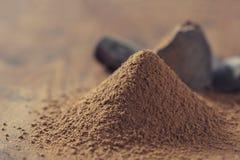 Chocolate, sólidos del cacao y polvo de cacao oscuros sobre fondo de madera Fotos de archivo libres de regalías