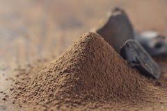 Chocolate, sólidos del cacao y polvo de cacao oscuros sobre fondo de madera Fotos de archivo
