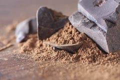 Chocolate, sólidos del cacao y polvo de cacao oscuros sobre fondo de madera Foto de archivo libre de regalías