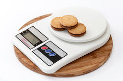 Chocolate sandwich biscuits on the digital scale Royalty Free Stock Images