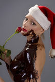 Chocolate santa rose. Attractive naked blond girl covered in chocolate wearing a santa hat and holding red rose Stock Image