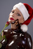 Chocolate santa rose. Attractive naked blond girl covered in chocolate wearing a santa hat and holding red rose Stock Photo