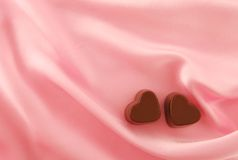 Chocolate on satin. Two chocolates hearts on the pink satin royalty free stock photo