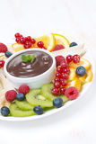 Chocolate sauce, fresh fruit and berries, vertical Stock Photos