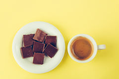 Chocolate on a saucer and a cup of coffee on a yellow surface Royalty Free Stock Image
