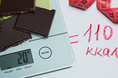 Chocolate, scales and calories. Scales show norm consumption of chocolate. beside the permissible calorie. The concept of proper nutrition Royalty Free Stock Photo