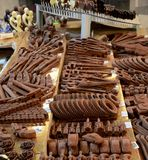 Chocolate sculpture carvings of guns pipes cars chains. Zagreb, Croatia - March 29, 2015: A display of a variety of chocolates shaped into different items in Royalty Free Stock Photography