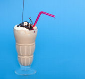 Chocolate shake with a drizzle of chocolate sauce. On a blue background Royalty Free Stock Images