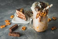 Chocolate shake with milk, dripping sauce, cream, cake and cookie. Chocolate shake with milk, dripping sauce, cream, cake royalty free stock photos