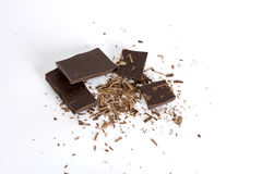 Chocolate shavings. Chocolate pieces and shavings on a white background royalty free stock photo