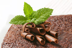 Chocolate shavings and mint on cake. Close up of chocolate shavings and mint on brownie cake Royalty Free Stock Photography