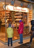 Chocolate shop. The Belgian chocolate is one of the best in the world. Two children look at chocolate shop with all its colorful boxes and a waterfall of stock image