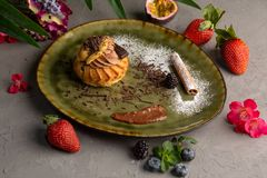 Chocolate shu on a green plate and berries royalty free stock photo