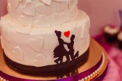 Chocolate silhouettes put on white wedding cake Stock Photo