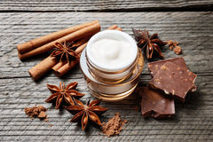 Chocolate skin treatment. Cosmetic jar with lotion, cocoa, anise, cinnamon sticks. Stock Photo