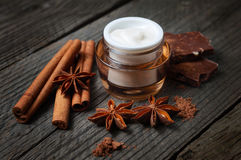 Chocolate skin treatment. Cosmetic jar with lotion, cocoa, anise, cinnamon sticks. Royalty Free Stock Photos