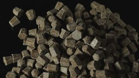 Chocolate slices cubes shaped isolated on black. stock video