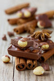 Chocolate slices with nuts, cinnamon sticks and anise star Stock Photography