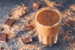 Chocolate smoothie with banana, decorated with chocolate chips on the dark background with pieces of chocolate and cocoa powder. H royalty free stock photos