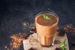 Chocolate smoothie with banana, decorated with mint leaf on the dark background with pieces of chocolate and cocoa powder. Healthy royalty free stock photo