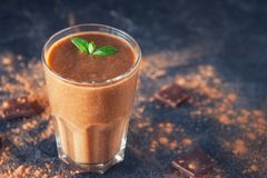 Chocolate smoothie with banana, decorated with mint leaf on the dark background with pieces of chocolate and cocoa powder. Healthy stock photos