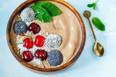 Chocolate smoothie bowl with cherry, mint and energy balls. Royalty Free Stock Images