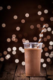 Chocolate smoothie or milkshake with party lights. Chocolate smoothie or milkshake with a sparkling bokeh of party lights in the background standing on a rustic stock photography