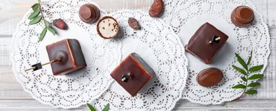 Chocolate souffle candy dessert with chocolate praline and cocoa beans on wooden background close up. Top view royalty free stock image