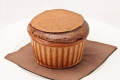 Chocolate souffle in ramekin. With a serviette served on a white plate Royalty Free Stock Images