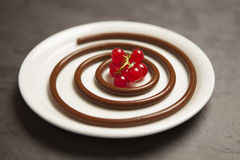 Chocolate spaghetti with red berries. Dessert, chocolate spaghetti with red berries on a white plate Stock Photos