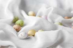 Chocolate specled Easter eggs in gauze fabric folds. Chocolate speckled Easter eggs in crisp sugar shell among delicate white gauze fabric folds that looks like Royalty Free Stock Photos