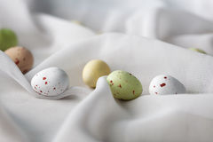 Chocolate specled Easter eggs in gauze fabric folds. Chocolate speckled Easter eggs in crisp sugar shell among delicate white gauze fabric folds that looks like Stock Image
