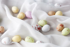 Chocolate specled Easter eggs in gauze fabric folds. Chocolate speckled Easter eggs in crisp sugar shell among delicate white gauze fabric folds that looks like Royalty Free Stock Photo