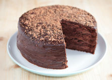 Chocolate sponge cake with buttercream frosting. Chocolate sponge cake with chocolate buttercream frosting and ganache on a plate on a wooden table stock images