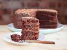Chocolate sponge cake with chocolate buttercream. Frosting and ganache on a plate on a wooden table, cut out piece, on a brick wall background royalty free stock photo