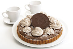Chocolate sponge cake with chocolate euro coin, two coffee cups in background Stock Photo
