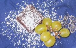 Chocolate sponge cake with icing sugar and grapes on the blue tablecloth.  Royalty Free Stock Photography
