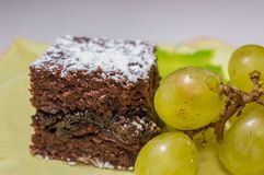 Chocolate sponge cake with icing sugar and grapes on the yellow tablecloth.  Stock Images
