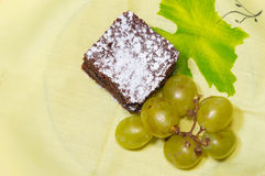 Chocolate sponge cake with icing sugar and grapes on the yellow tablecloth.  Stock Image
