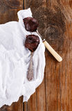 Chocolate spread on spoons on wooden background. Chocolate spread on two spoons on rustic wooden background royalty free stock photos