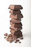 Chocolate squares. Stack of chocolate squares with small pieces on the side stock photos