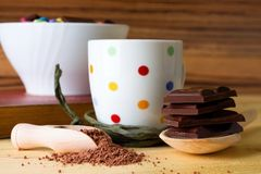 Chocolate squares in front of spotted cup stock photos