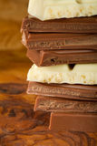 Chocolate stack of dark and white chocolate with brown background Royalty Free Stock Photography