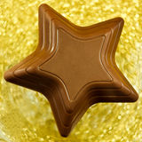 Chocolate star. Macro view of chocolate star on blurred golden background Stock Images