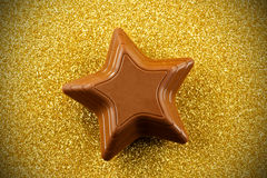 Chocolate star on sparkly background Royalty Free Stock Photo