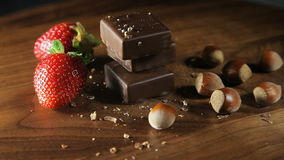 Chocolate, strawberries and nuts. On a wooden background. It slowly revolves around its axis stock video footage