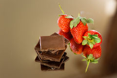 Chocolate and strawberry. Black chocolate along some fresh strawberries stock photo