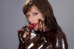 Chocolate strawberry brunette. Attractive naked brunette girl covered in chocolate while eating strawberry Royalty Free Stock Image