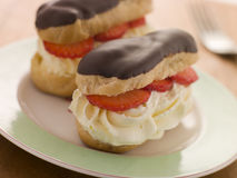 Chocolate and Strawberry filled eclairs stock photos